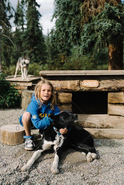 Boy bonding with sled dog