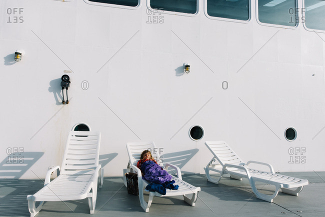 Girl on lounge a chair on ferry deck