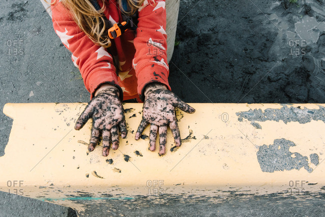 Girl with mud covered hands