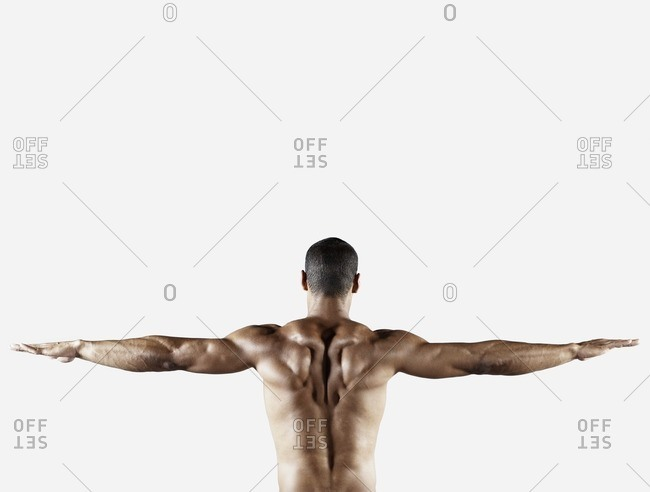 Bare chested mixed race man with arms outstretched