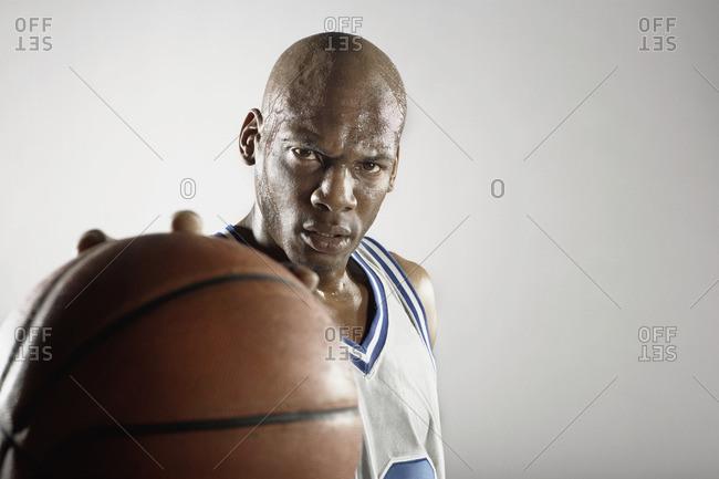 Sweating Hispanic basketball player holding basketball