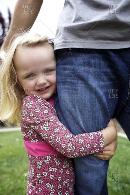 Caucasian girl hugging father's leg