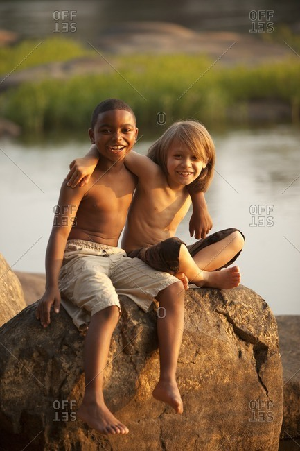 Smiling boys hugging on rock near lake