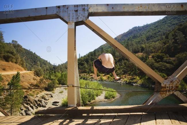 Caucasian man jumping into river from bridge