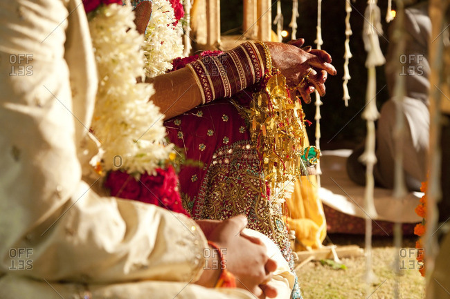 Couple in ornate, traditional Indian wedding clothing