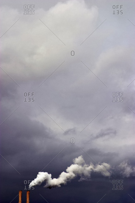 Overcast sky and smoke stacks billowing smoke
