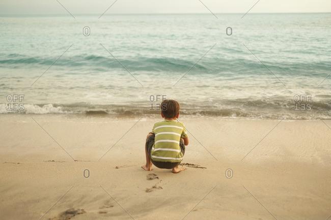 Mixed race boy squatting on beach playing