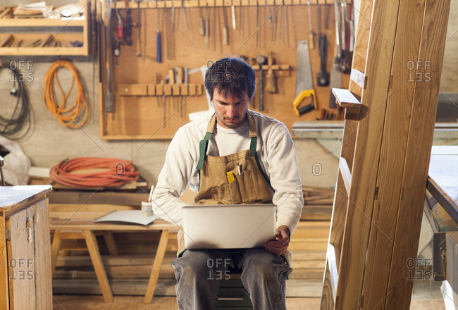 Caucasian carpenter using laptop in workshop