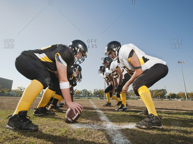 Football players crouching on football field
