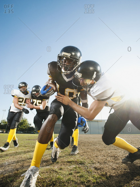 Football player tackling player on football field