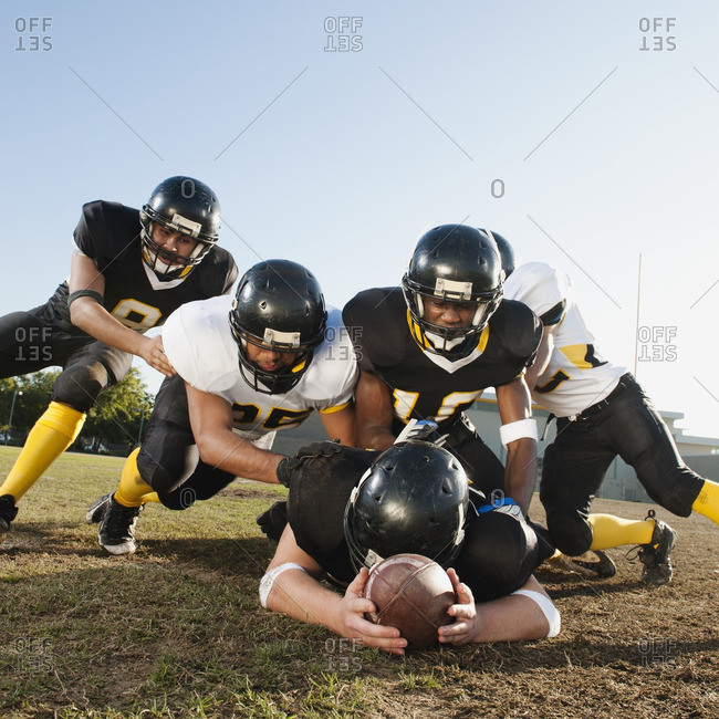 Football players tackling player on football field
