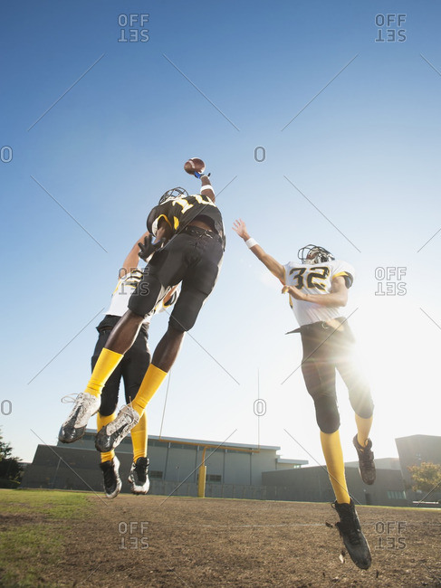 Football player catching ball on football field