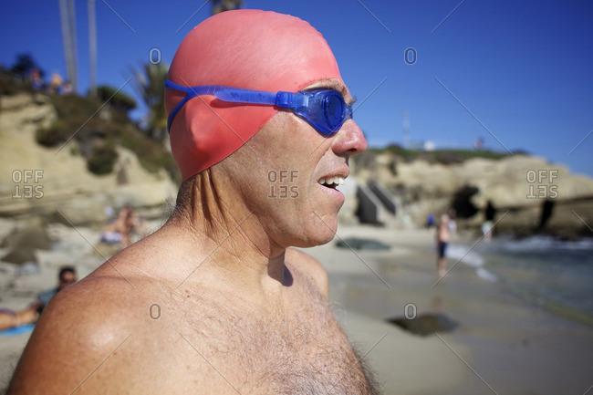 Caucasian man in swim cap and goggles on beach
