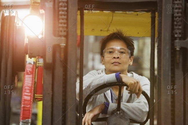 Mixed race worker driving a forklift in factory