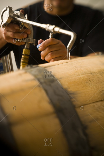 Man pouring water into wooden keg