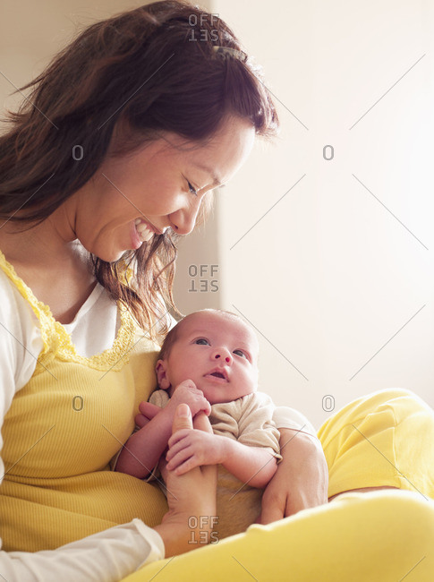 Mother holding newborn baby in her lap