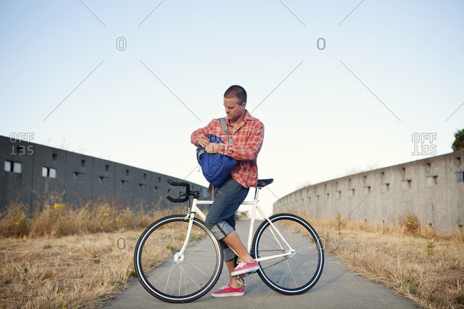 Bicycle messenger stopping on urban path