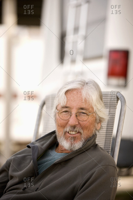 Senior Caucasian man sitting outside motor home