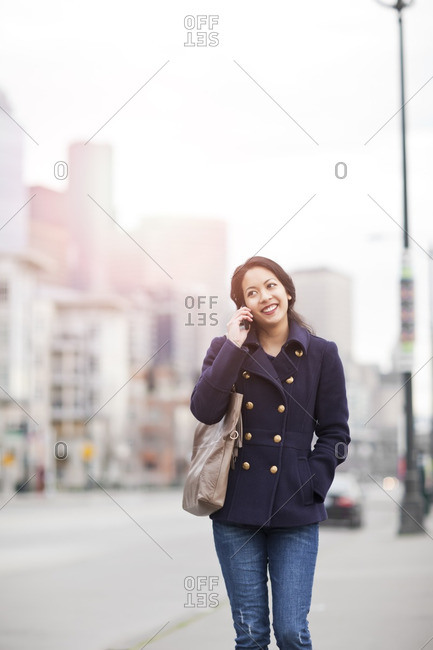 Mixed race woman walking and talking on cell phone