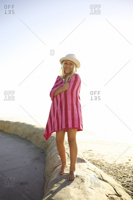 Mixed race girl at beach wrapped in towel