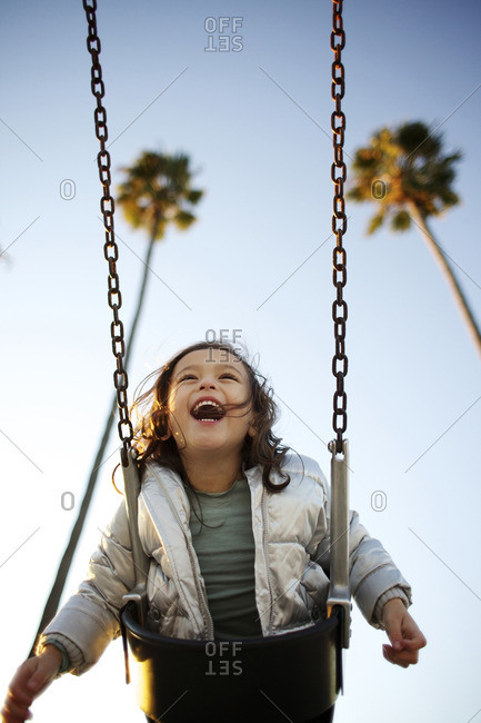 Laughing mixed race girl swinging