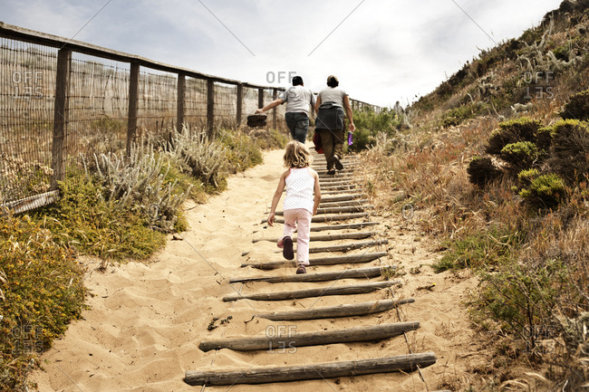Family walking up sandy staircase