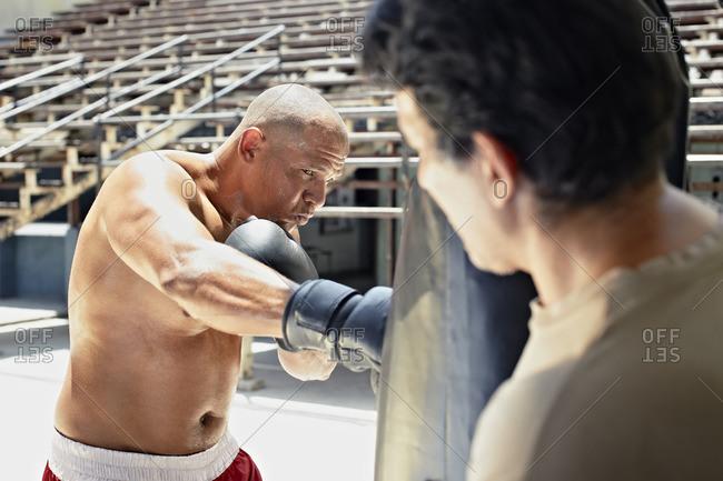Hispanic boxer training in gym