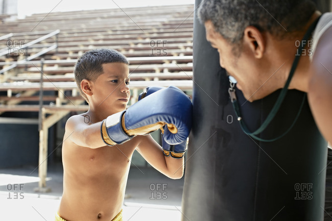 Hispanic boy boxing punching bag