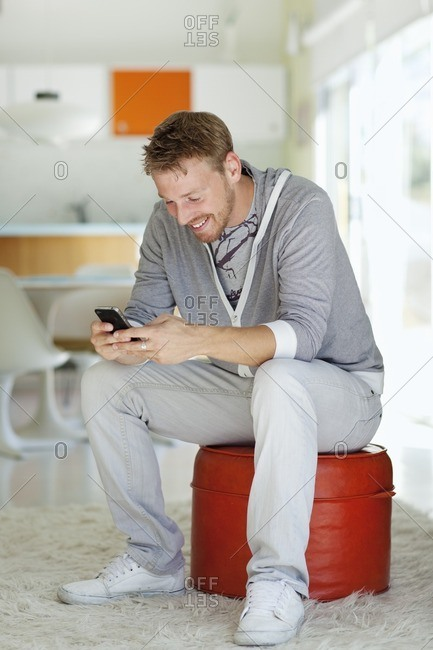 Caucasian man text messaging on cell phone in living room