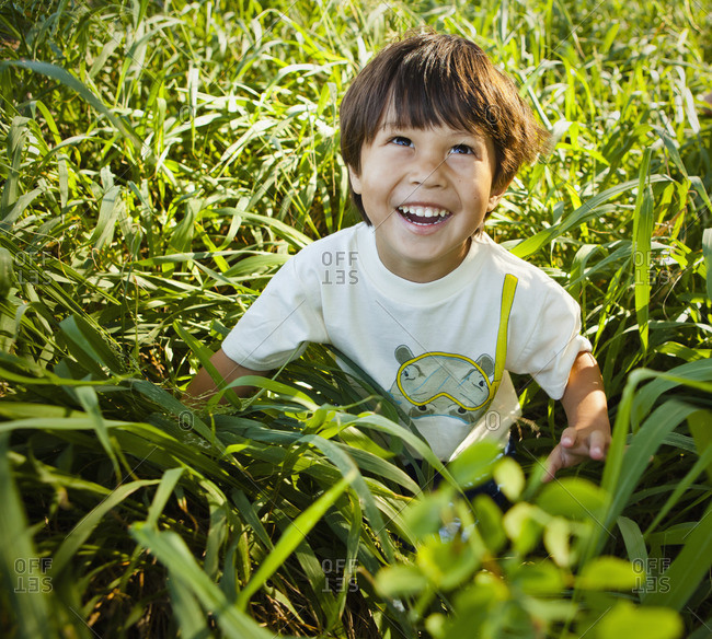 Grinning mixed race boy sitting in long grass
