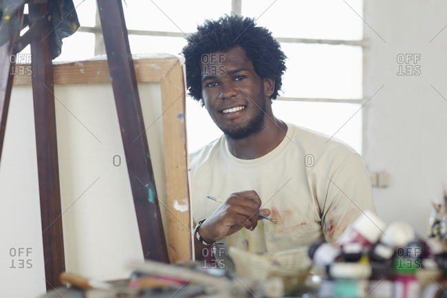 Black artist painting in art studio