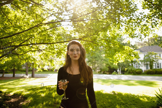 Caucasian woman drinking white wine in park