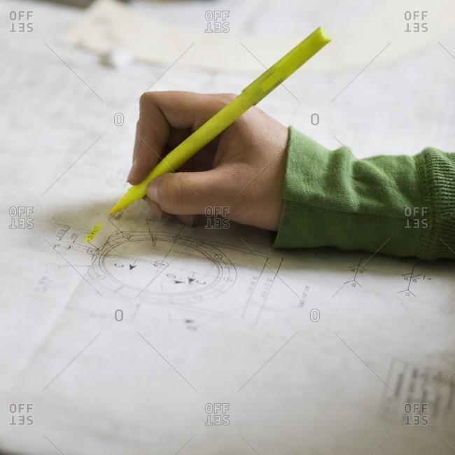 Hispanic woman highlighting drawing