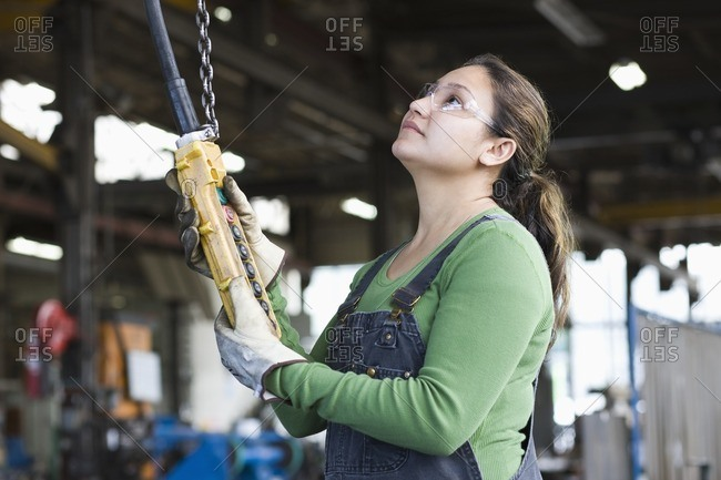 Hispanic worker using control panel in warehouse