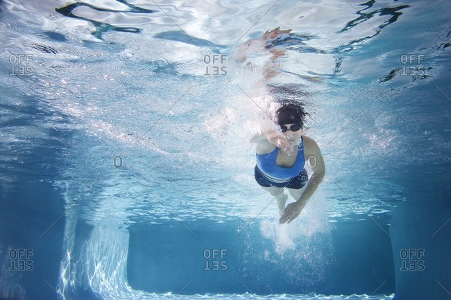 Caucasian woman swimming in swimming pool