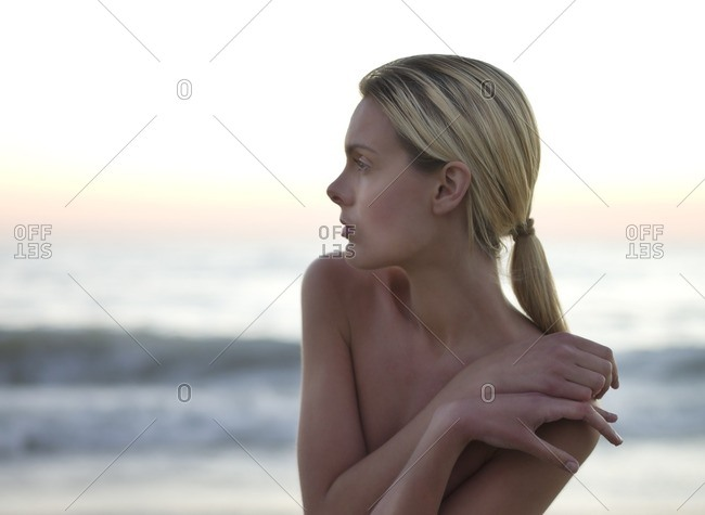 Topless Caucasian woman standing on beach