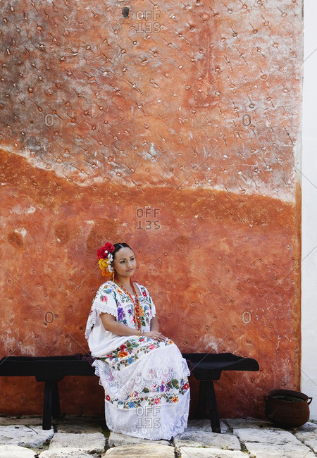 Woman sitting on bench in traditional Mexican clothing