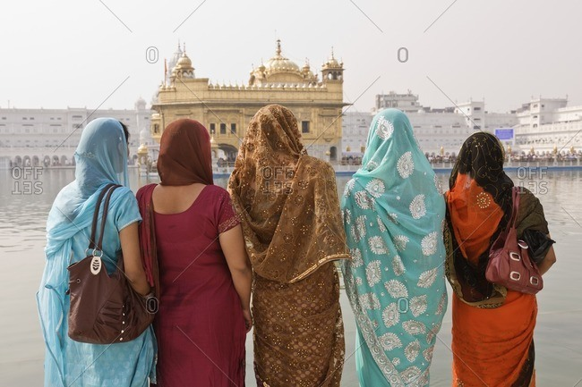 Women in traditional Indian clothing looking at ornate building