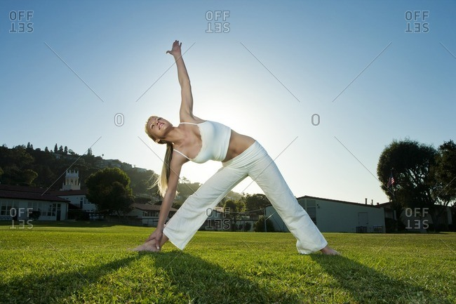 Caucasian woman practicing yoga in field