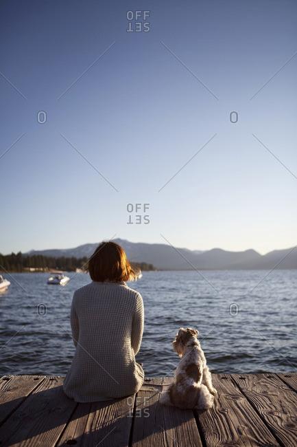 Woman and miniature schnauzer sitting on pier