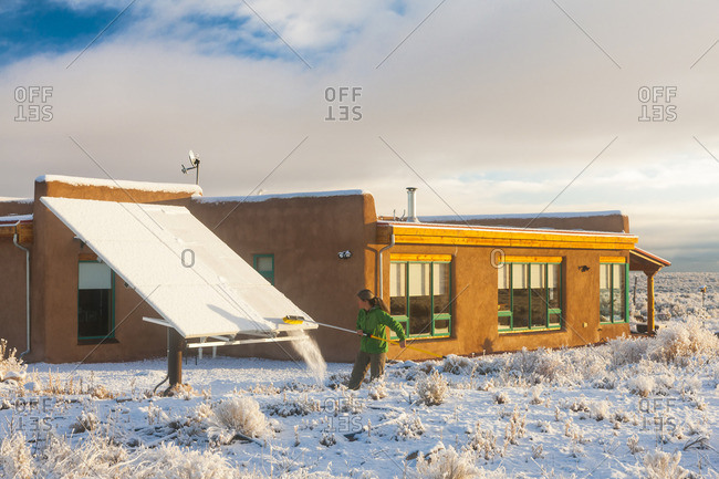 Woman taking snow off solar panel