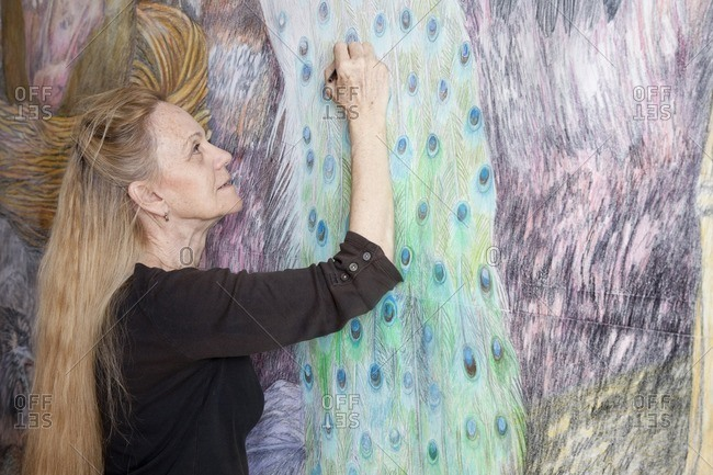 Caucasian woman drawing mural on wall