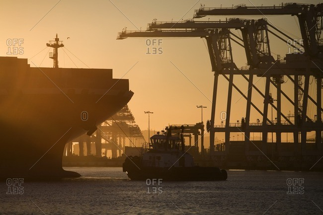 Oakland, CA, USA - August 27, 2008: Tugboat and container ship of port of Oakland