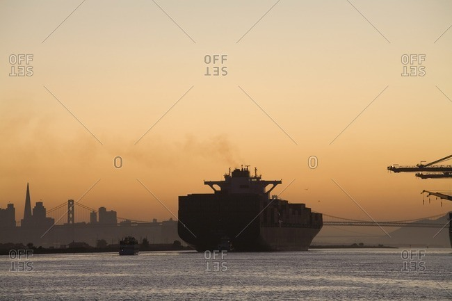 Oakland, CA, USA - August 27, 2008: Tugboat and container ship in port of Oakland