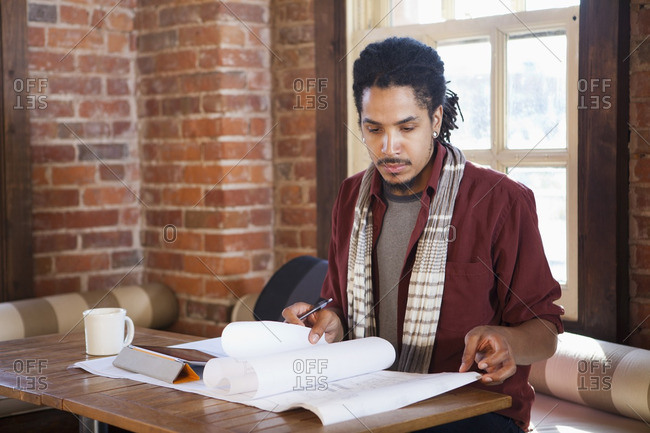 Mixed race businessman working in coffee shop