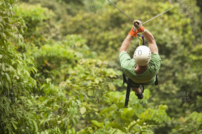 Caucasian man on zip line in forest