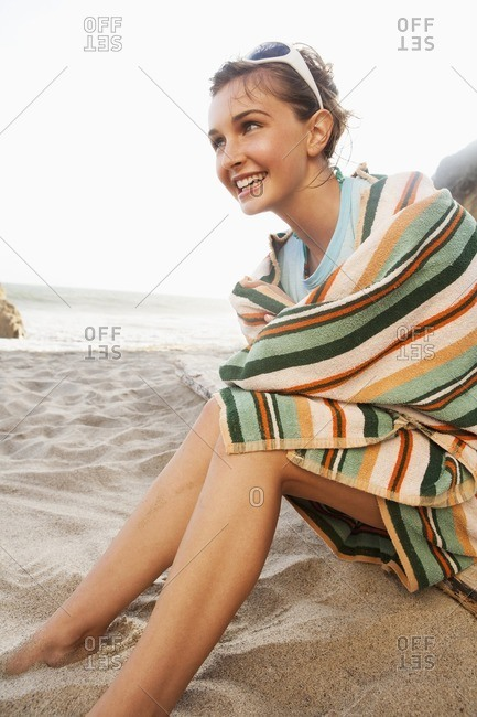 Caucasian woman sitting on beach wrapped in a towel