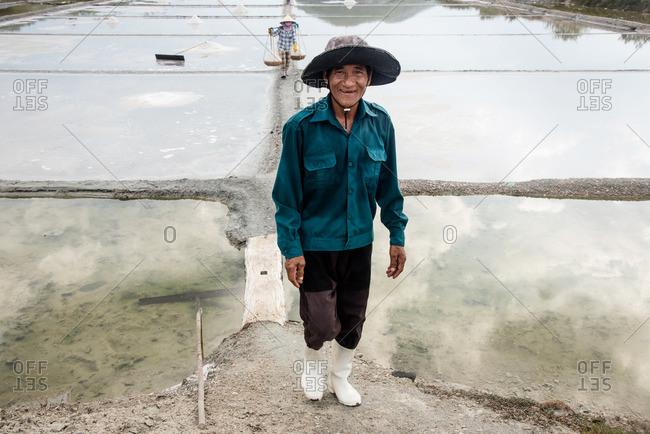 Vietnam - September 6, 2016: Workers on a salt farm
