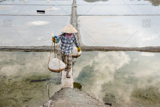 Woman carrying baskets of salt