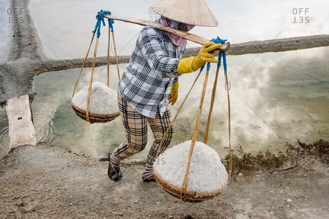 Woman carrying baskets of salt on farm